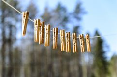 Clothespins for clothes and clothes hang against the blue sky on a Sunny day royalty free stock photography