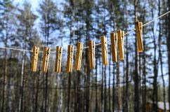Clothespins for clothes and clothes hang against the blue sky on a Sunny day on a narrow stock photography