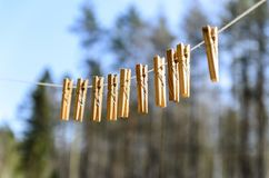 Clothespins for clothes and clothes hang against the blue sky on a Sunny day on a narrow stock image