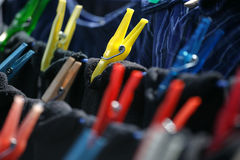 Clothespins on clothesline. Colourful clothespins hanging dark laundry to dry royalty free stock photography