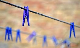 Clothespins hanging at two clotheslines stock photos