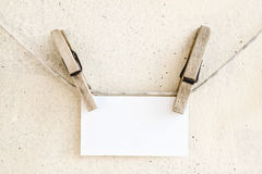 Clothespins holding blank white paper card Stock Photos