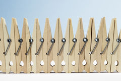 Clothespins placed upright forming a fence. A fence formed by spring-type wooden clothespins on white floor and blue background Royalty Free Stock Images