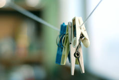 Clothespins on a rope. White, grey, blue, green clothespins hanging on a rope. Shallow depth of the field royalty free stock images