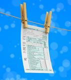 Clothespins on rope with Tax form 1040. Image with clipping path Royalty Free Stock Photo