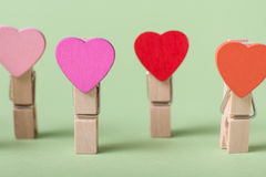 Clothespins in a row. Colored heart shaped clothespin in row on greenery background Royalty Free Stock Photography