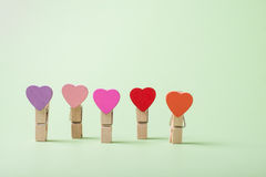 Clothespins in a row. Colored heart shaped clothespin in row on greenery background Stock Image