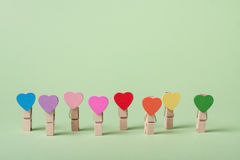Clothespins in a row. Colored heart shaped clothespin in row on greenery background Royalty Free Stock Images