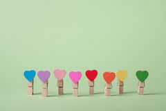 Clothespins in a row. Colored heart shaped clothespin in row on greenery background Royalty Free Stock Image