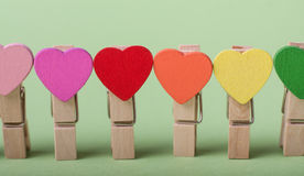 Clothespins in a row. Colored heart shaped clothespin in row on greenery background Royalty Free Stock Photos