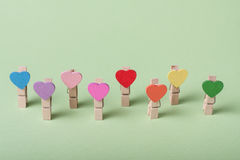 Clothespins in a row. Colored heart shaped clothespin in row on greenery background Royalty Free Stock Photo