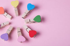 Clothespins in a row. Colored heart shaped clothespins compose circle on pink background Stock Photos