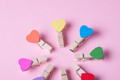 Clothespins in a row. Colored heart shaped clothespins compose circle on pink background Stock Image