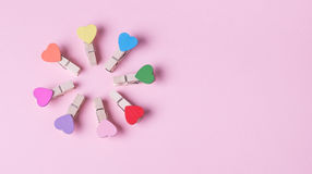 Clothespins in a row. Colored heart shaped clothespins compose circle on pink background Royalty Free Stock Image