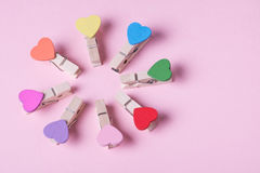 Clothespins in a row. Colored heart shaped clothespins compose circle on pink background Royalty Free Stock Photos