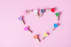 Clothespins in a row. Colored heart shaped clothespins compose heart on pink background Royalty Free Stock Image
