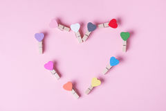 Clothespins in a row. Colored heart shaped clothespins compose heart on pink background Royalty Free Stock Images