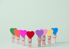 Clothespins in a row. Colored heart shaped clothespins in row on greenery background Royalty Free Stock Image