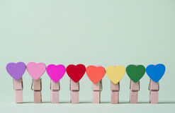 Clothespins in a row. Colored heart shaped clothespins in row on greenery background Royalty Free Stock Photos