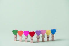 Clothespins in a row. Colored heart shaped clothespins in row on greenery background Stock Images