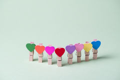 Clothespins in a row. Colored heart shaped clothespins in row on greenery background Stock Photography