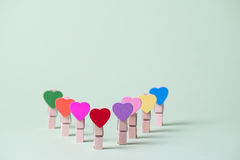 Clothespins in a row. Colored heart shaped clothespins in row on greenery background Stock Photos
