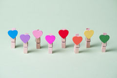 Clothespins in a row. Colored heart shaped clothespins in row on greenery background Royalty Free Stock Images