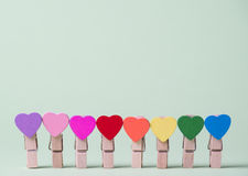Clothespins in a row. Colored heart shaped clothespins in row on greenery background Royalty Free Stock Photo