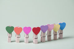Clothespins in a row. Colored heart shaped clothespins in row on greenery background Stock Image