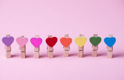 Clothespins in a row. Colored heart shaped clothespins in row on pink background Stock Photo