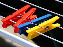 Clothespins. Some colored pegs hanging by a thread Royalty Free Stock Photo
