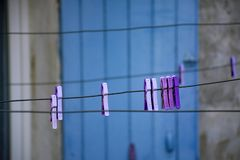 Clothespins on washing rope, hanging outside in small Provencal village in lavender color. Nd blue door stock image