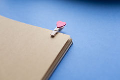 Clothespins z sercami są Notepad Błękitny tło papier Fotografia Stock