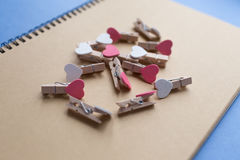 Clothespins z sercami są Notepad Błękitny tło papier Zdjęcie Royalty Free