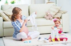 愉快的家庭怀孕的母亲和准备clothi的儿童女儿 库存照片