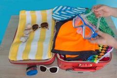 clothing öppen röd resväska Kvinna som sätter kläder i resväskan, closeup Arkivbilder