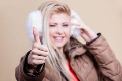 Woman wearing winter furry earmuffs having fun. Clothing accessories, seasonal clothes concept. Woman wearing jacket and winter furry warm earmuffs showing thumb Stock Image