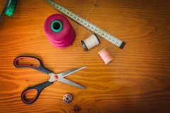 Clothing accessories,thread, scissors and measuring tape. Clothing tools and accessories, scissors, measuring tape, and a roll of thread royalty free stock image
