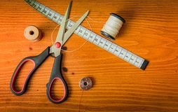Clothing accessories,thread, scissors and measuring tape. Clothing tools and accessories, scissors, measuring tape, and a roll of thread royalty free stock photos