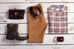 Clothing and accessories on a wooden background. Beautiful set of casual menswear. Clothing and accessories on a wooden background Stock Photography