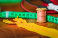 Clothing accessories, zipper, thread, scissors and measuring tap. Clothing tools and accessories, scissors, measuring tape, and a roll of thread stock photography