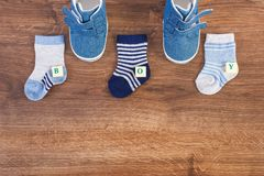 Clothing for baby and inscription boy, expecting for newborn concept, place for text on rustic board. Blue clothing for baby and inscription boy, expecting for stock photo