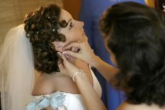 Clothing of the bride. The girlfriend of the bride helps her to put on ear rings for wedding ceremony Royalty Free Stock Image