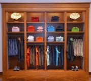 Clothing Business - Wooden Cabinet with Clothes Stored, Colorful Wardrobe. Colorful wardrobe with colorful clothes stored in a  wooden cabinet Stock Photography