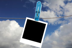 Clothing clamp with Blank Polaroid Frame. On the sky Stock Image