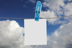 Clothing clamp and white paper. On sky Stock Images