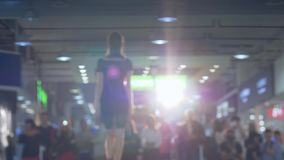 Clothing collection, professional model defiles the podium in dress and high heels in backlight