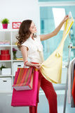 In clothing department. Portrait of pretty woman choosing new dress in clothing departmant Stock Photo