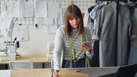 Clothing design entrepreneur is checking paper sewing drafts and looking at smartphone. She is examining every cutout. And thinking about future garment. Modern stock video