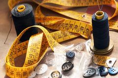Clothing designers equipment. With a tape measure, yarn or cotton, mad assorted buttons in a close up background view Stock Photos